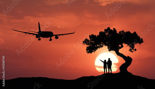Poster de jardin Rouge traffic People under the crooked tree and airplane on the background of orange sky with sun. Silhouette of a couple on the hill, tree, passenger aircraft and colorful sky with clouds at sunset. Landscape