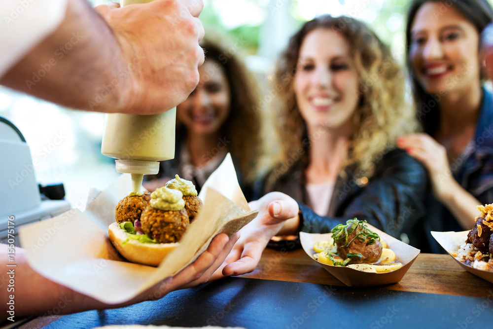 Fototapety, obrazy: Three beautiful young women buying meatballs on a food truck.