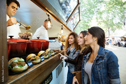 Three beautiful young women buying meatballs on a food truck.