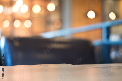 Fotografiet  Wooden table and chair in cafe with blur bokeh abstract vintage background
