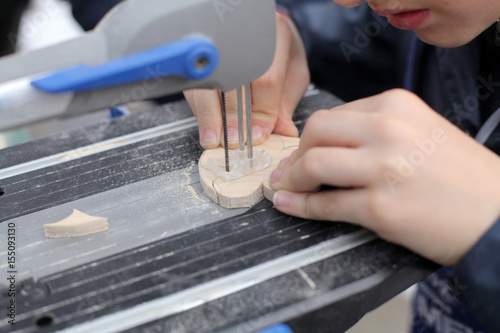 Small boy hands working with fret to saw board  Classes for