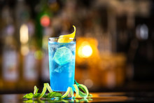 Closeup Glass Of Blue Lagoon Cocktail Decorated With Lime At Festive Bar Counter Background.
