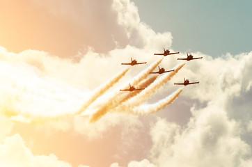 Panel Szklany Do pokoju chłopca Aircraft fighter jets smoke the background of sky and sun.
