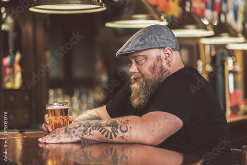 Photo Man drinking a beer in a bar