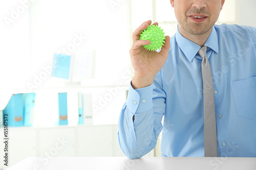 Man with stress ball in office