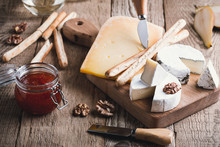 Cheese Platter With Wine, Jam And Walnuts On Wooden Board