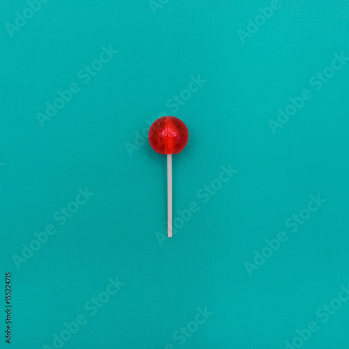 Lollipop Flat lay Minimal concept Red round lollipop is lying on a light blue ba Poster Mural XXL