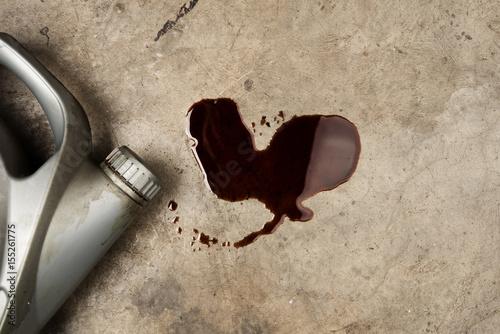 Fotografia Black old oil of car motor engine used spill drop on concrete floor with bottle