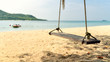 The beach swing is made of wood attached to the coconut trees No body