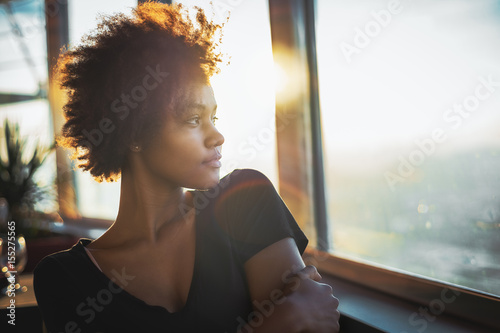 Fotografía  Curly charming young afro american tourist female in black dress is sitting in l
