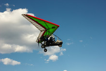 The Motorized Hang Glider Flying On Background Blue Sky With Clouds.