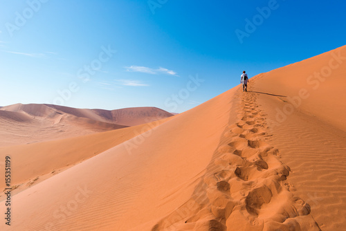 Tourist walking on the scenic dunes of Sossusvlei, Namib desert, Namib Naukluft National Park, Namibia Fotobehang