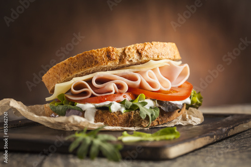 Poster Snack Tasty sandwich with ham, cheese, tomato and lettuce on wooden background