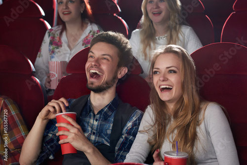 Carta da parati  Positive couple of two, boyfriend in checked shirt and girlfriend in gray blouse surprised smiling, watching comedy movie together, holding red cup with cola