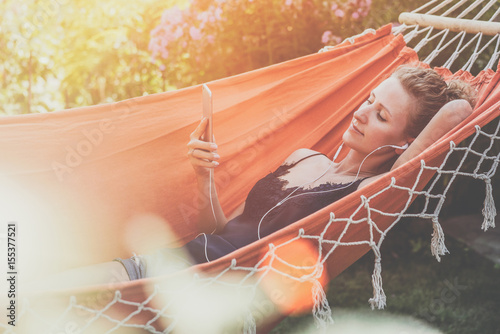 Fotografie, Obraz  Summer day, young woman lying in orange hammock in park and listening to music on smartphone