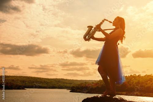 Fototapeta Kobieta bawić się saksofonu sax przy zmierzchem