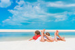 Little girls having fun at tropical beach lying together on the seashore