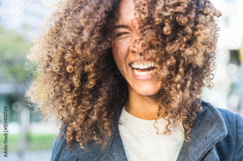 Curly woman laughing and shaking head Fototapeta