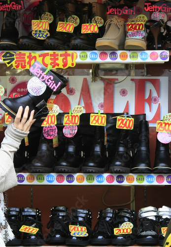 A clerk arranges goods at a shoes store at a shopping