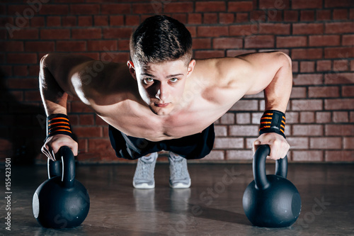 Spoed Foto op Canvas Fitness Sport. Young athletic man doing push-ups. Muscular and strong guy exercising.