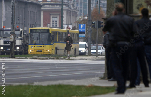 A gunman with an automatic weapon walks in Sarajevo, after he fired