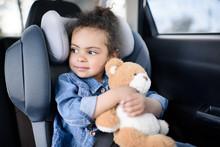 Little Girl Holding Teddy Bear While Sitting In Car