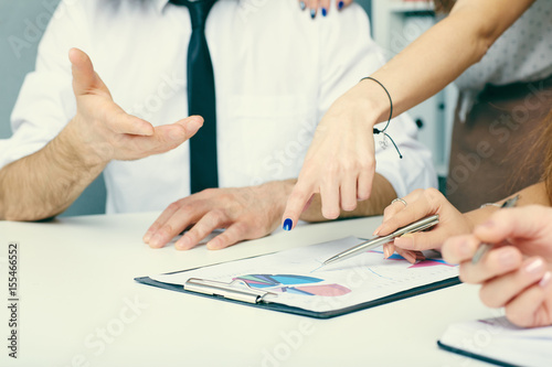 Fototapety, obrazy: Group of business people looking at the clipboard with graphics.