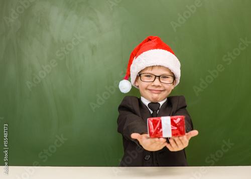 Fényképezés  Happy boy in red christmas hat with gift near empty green blackboard