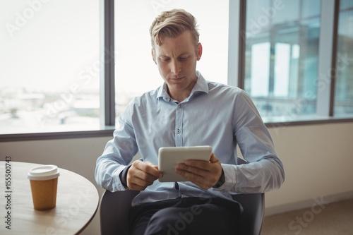 Fotografia  Attentive executive using digital tablet at table