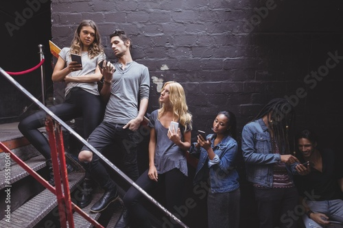 Young friends using mobile phone at nightclub staircase Canvas
