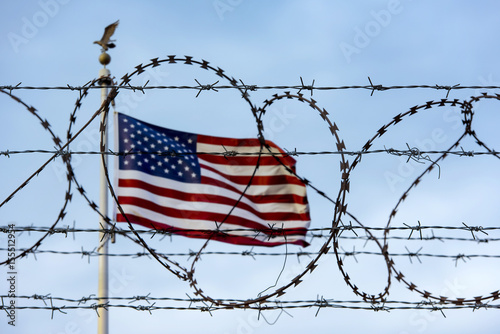 Photo  American flag and barbed wire, USA border