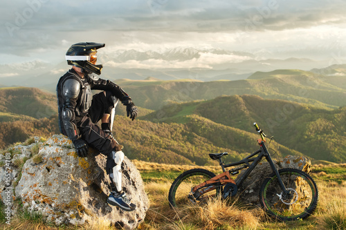 Stampa su Tela A professional downhill rider sits on a stone resting after a tense race on a mt