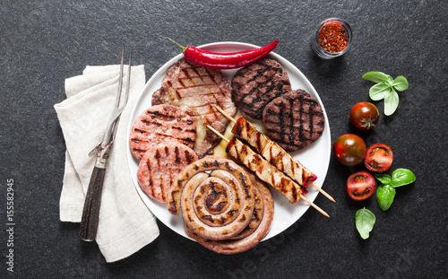 Plakat Mięso z grilla. Mięso z grilla na talerzu, liści bazylii, pomidorów i widelca do mięsa