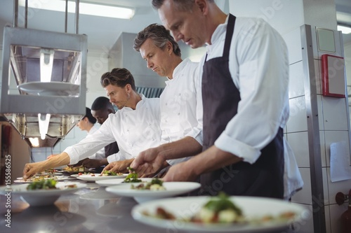 Team of chefs garnishing meal on counter