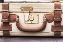 An Old Vintage Suitcase With Leather Straps