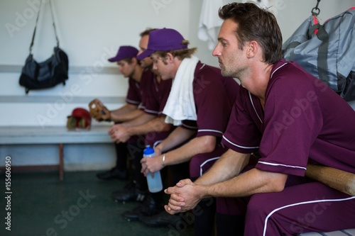 Photo  Side view of tired basball players sitting on bench