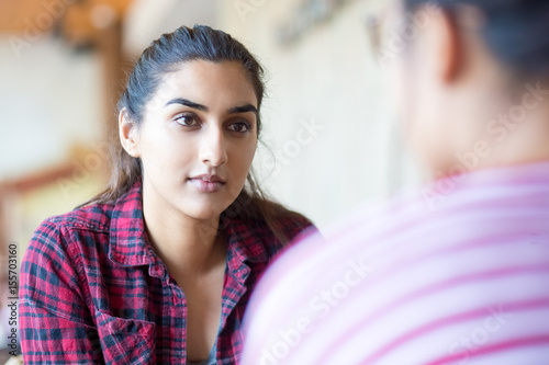 Concentrated Indian woman talking to friend