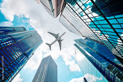 Foto Airplane flying over business skyscrapers