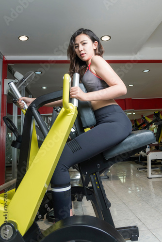 Photo  Asian woman using fitness machine at the gym.