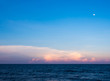 Clouds and moon in sunset sky over sea