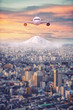 Retouch Mt.Fuji covered with snow and Japan cityscape with airplane on the sky in twilight