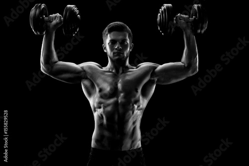 Fényképezés  Black and white studio shot of a handsome young shirtless weightlifter exercising with dumbbells lifting weights athlete athletics activity lifestyle motivation power sports confidence focusing