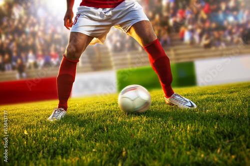 Zdjęcie XXL Gracz piłki nożnej z czerwonymi skarpetami w pozycji dryblować ... Stopień zamazuje się za nim.