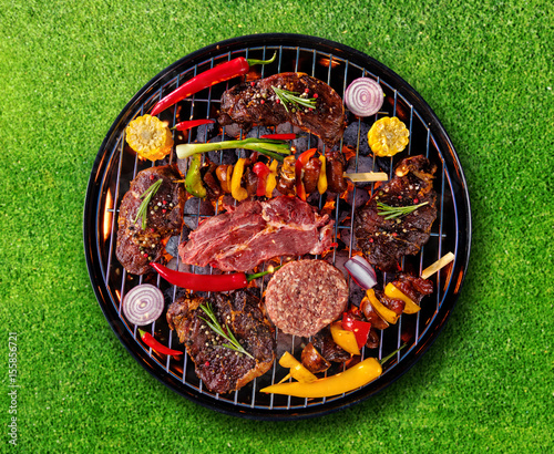 Aluminium Prints Grill / Barbecue Top view of fresh meat and vegetable on grill placed on grass