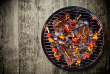Top View Of Fresh Meat And Vegetable On Grill Placed On Wooden Floor