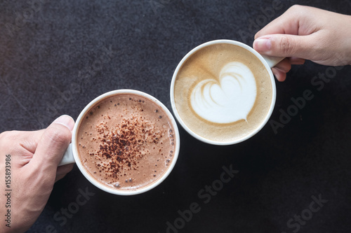 In de dag Chocolade Top view image of man and woman's hands holding coffee and hot chocolate cups with wooden table background