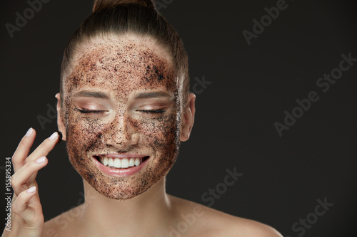 Fotografie, Obraz Face Skin Scrub. Smiling Girl Applying Coffee Mask Scrub On Skin