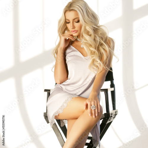 Photo Young stunning and sexy tanned blonde woman with long curly hair wearing bright micro tunic dress and sitting in high directors chair
