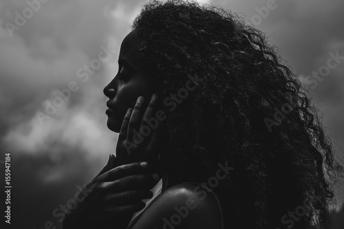Foto  Portrait of a beautiful ethnic african american woman with clouds in the backgro