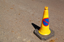 Yellow No Parking Cone On The Road With A Shadow And Space For Text.